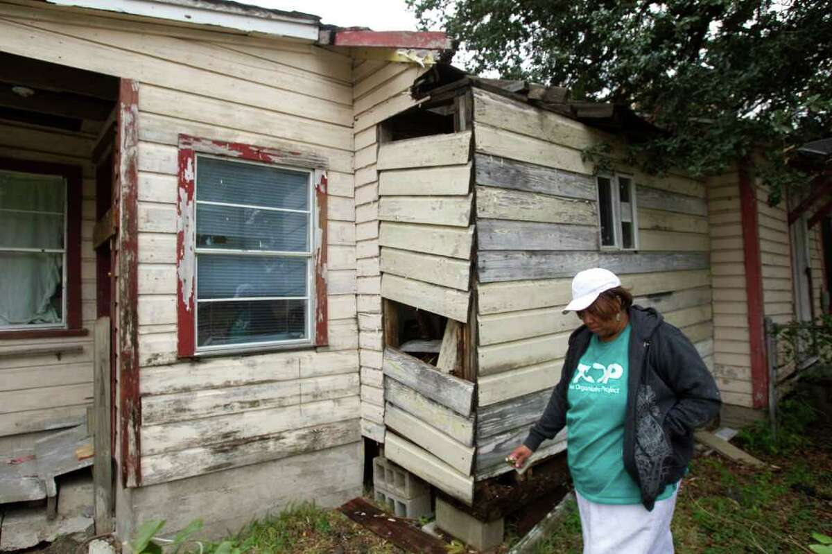 BRETT COOMER : CHRONICLE NEEDS HELP: Sharon Thomas, 56, walks around her Hurricane-Ike damaged home in Independence Heights. Thomas hopes she can finally get her name on a list for repair money.
