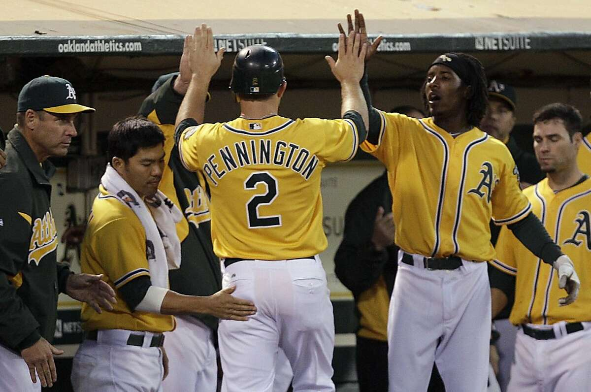 Oakland Athletics' Cliff Pennington (2) is congratulated by teammates Kurt Suzuki, left, and Jemile Weeks after scoring against the Tampa Bay Rays during the fifth inning of a baseball game Tuesday, July 26, 2011, in Oakland, Calif.