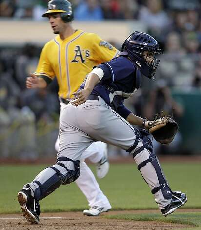 Oakland Athletics' Scott Sizemore, left, scores behind Tampa Bay Rays catcher Robinson Chirinos during the third inning of a baseball game Tuesday, July 26, 2011, in Oakland, Calif. Photo: Ben Margot, AP