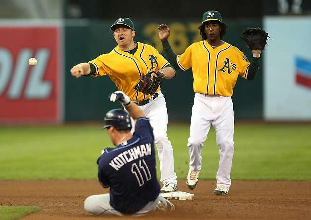 OAKLAND, CA - JULY 26:  Cliff Pennington #2 of the Oakland Athletics throws to first base as Casey Kotchman #11 of the Tampa Bay Rays slides into second base on a double play ball hit by B.J. Upton #2 of the Rays in the fourth inning at O.co Coliseum on July 26, 2011 in Oakland, California. Photo: Jed Jacobsohn, Getty Images