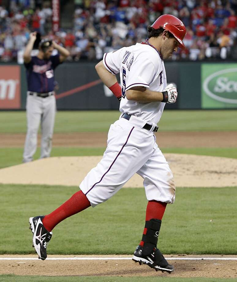Texas Rangers' Ian Kinsler heads toward home plate after hitting a three-run home run off of Minnesota Twins' Nick Blackburn, rear, in the third inning of a baseball game, Monday, July 25, 2011, in Arlington, Texas. The shot scored Chris Davis and Mike Napoli. Photo: Tony Gutierrez, AP