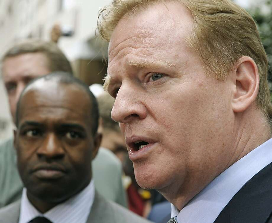 NFLPA Executive Director DeMaurice Smith, left, looks on as NFL football Commissioner Roger Goodell speaks  outside the NFL Players Association headquarters in Washington, Monday, July 25, 2011, after the NFL Players Association executive board and 32 team reps voted unanimously Monday to approve the terms of a deal with owners to the end the 4½-month lockout.. Photo: Cliff Owen, AP