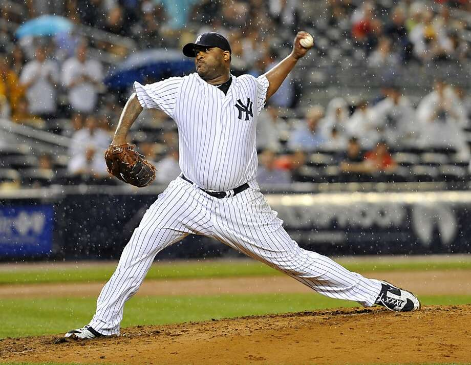 The New York Yankees' CC Sabathia pitches in the rain in the seventh inning against the Seattle Mariners at Yankee Stadium in New York on Tuesday, July 26, 2011. (David Pokress/Newsday/MCT) Photo: David Pokress, MCT