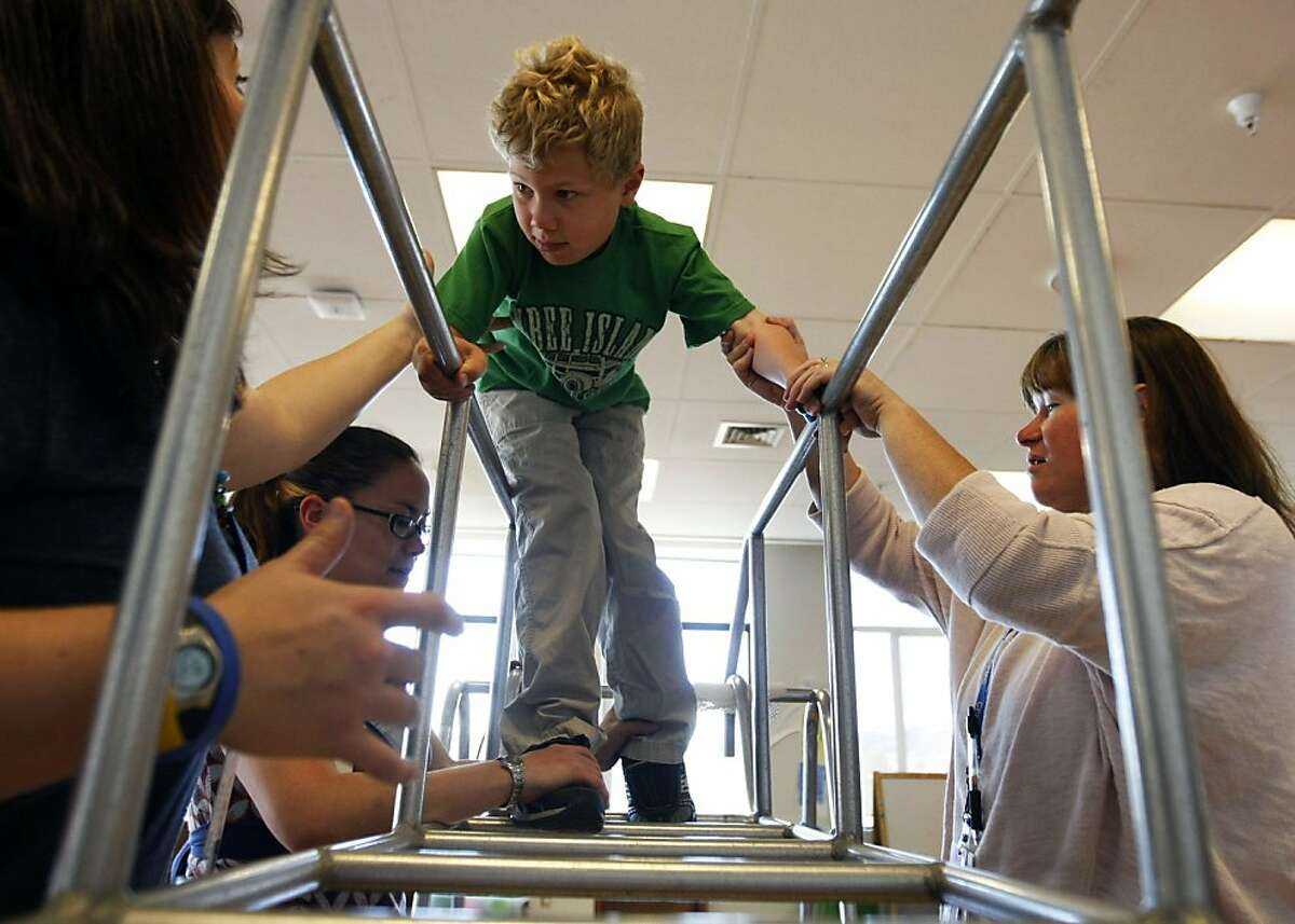 Bennett Vernick age 7 gets help from his therapist while negotiating the obstacle course. California Pacific Medical Center is hosting a