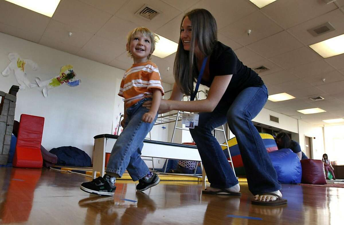 Allison Mayer a volunteer at Camp Bennett helps Julian Gaube age 3 with his motor skills. California Pacific Medical Center is hosting a