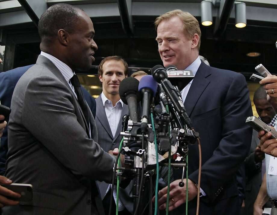 DeMaurice Smith, Executive Director of the NFL Players Association, left, and NFL Commissioner Roger Goodell shake hands as New Orleans Saints quarterback Drew Brees looks on at center during a news conference at the NFL Players Association, Monday, July25, 2011, in Washington, after the NFL Players Association executive board and 32 team reps voted unanimously Monday to approve the terms of a deal with owners to the end the 4 1/2-month lockout. Photo: Carolyn Kaster, AP