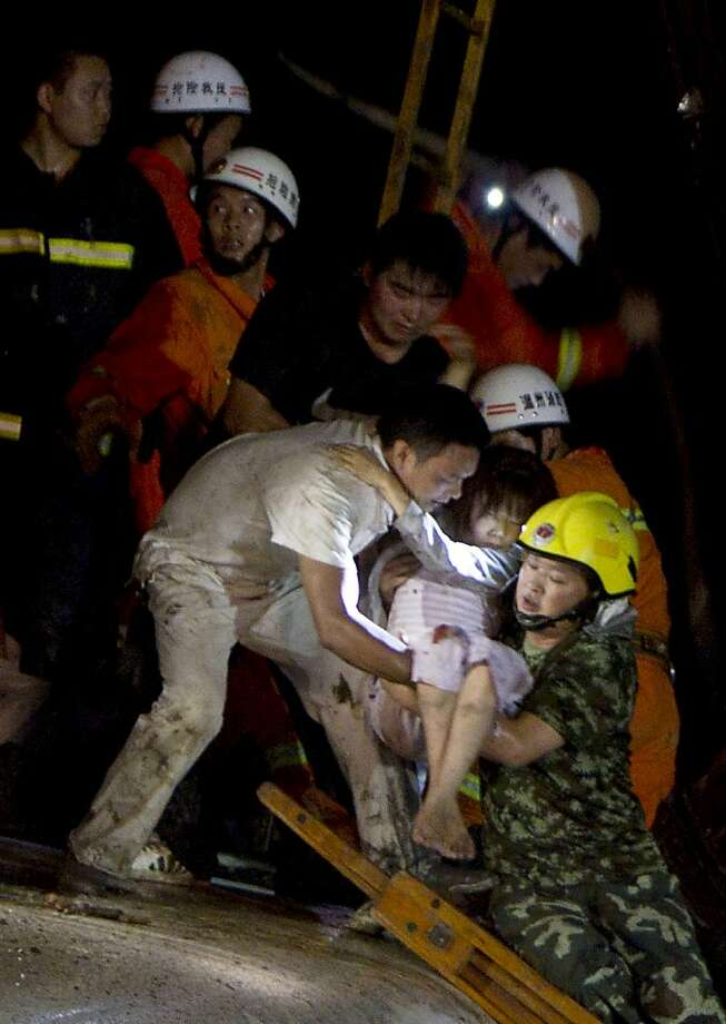 Chinese rescue workers carry an injured girl as they tend to the victims of a high-speed train accident on July 23, 2011, near Wenzhou. Two train cars derailed and fell off a bridge after the train, already crippled by a lightning strike, was hit from behind by another express, according to state media reports. The train, which was travelling between the eastern Chinese cities of Wenzhou and Hangzhou, went off the rails around 8:30pm (1230 GMT), Xinhua news agency reported, citing local firefighting sources. At least 11 people were killed. CHINA OUT Photo: Str, AFP/Getty Images