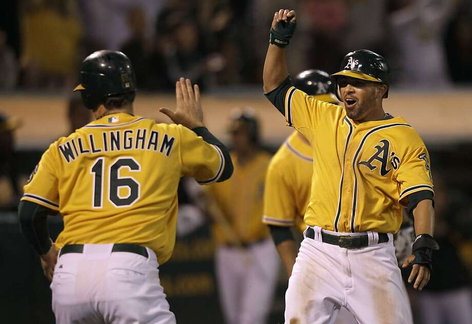 Oakland Athletics' David DeJesus, right, and Josh Willingham celebrate after both scored on Conor Jackson's double against the Tampa Bay Rays in the seventh inning of a baseball game in Oakland, Calif., Monday, July 25, 2011. Photo: Jeff Chiu, AP