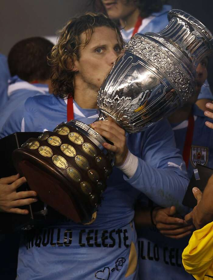 Uruguay's Diego Forlan holds the Copa America at the end of the final soccer match with Paraguay in Buenos Aires, Argentina, Sunday, July 24, 2011. Uruguay won the Copa America for a record 15th time after beating Paraguay 3-0  with two goals scored by Forlan and one by Luis Suarez. Photo: Roberto Candia, AP
