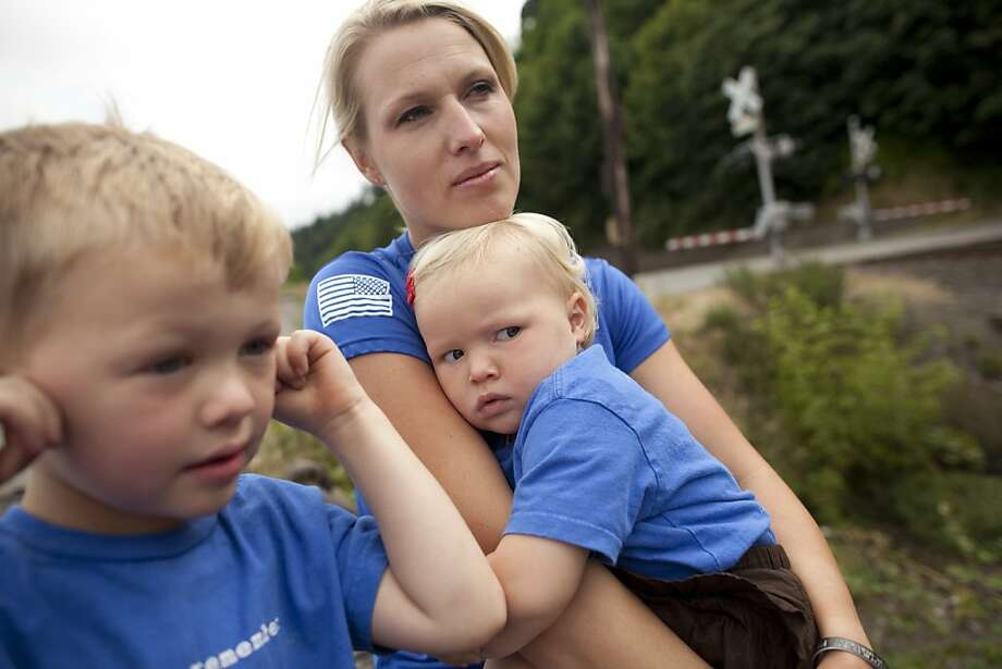 "Lisa Hallett sits with her children, Jackson, left, and Heidi, at Solo Point, a beach near her home where she often trains for running marathons, in Fort Lewis, Washington, on Thursday, July 21, 2011.  Lisa Hallett's husband, Army Capt. John Hallett, was killed in 2009, and to deal with her grief she started running. She found it helped calm her mind, so she asked other Army wives to run with her -- and now, three years later, she has a regular group of military-associated men and women she runs with every Saturday to show support for our troops, both dead and alive, and has founded a nonprofit called ""Wear Blue, Run to Remember"". Hallett is coming to San Francisco on Sunday, July 31, with about 100 of her running pals to run in the S.F. Marathon -- and she is pushing herself to run 52.4 miles instead of the usual 26.2 to honor her husband.  CREDIT: Mike Kane for the San Francisco Chronicle Photo: Mike Kane, Special To The Chronicle"