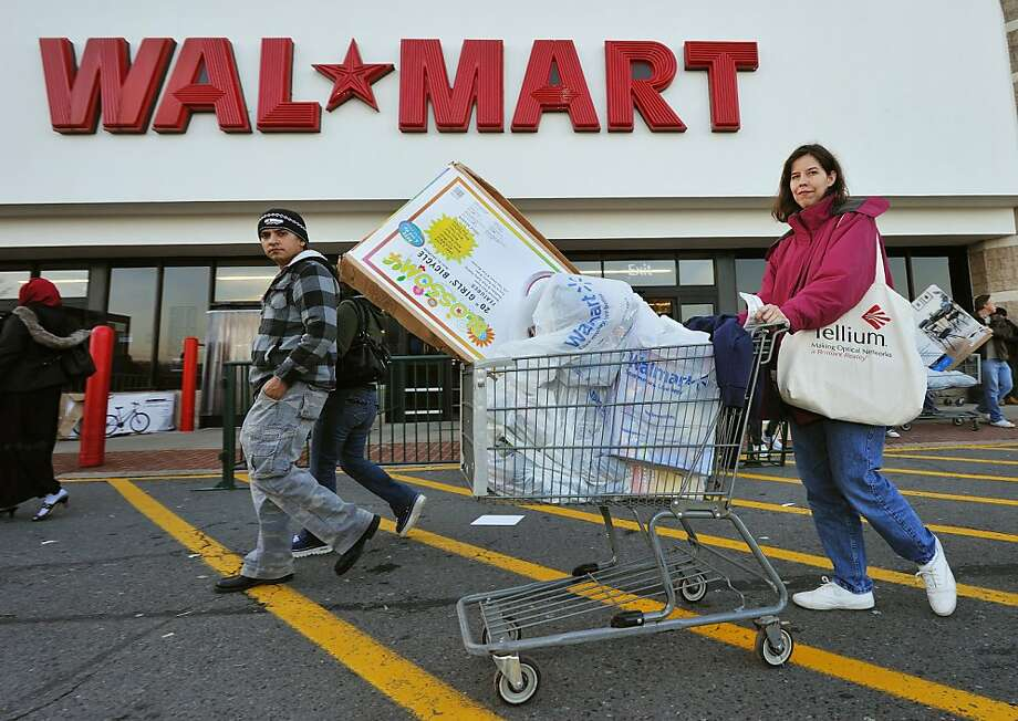 (FILES)Holiday shoppers leave the Wal-Mart store in Fairfax, Virginia, in this November 27, 2009 file photo. Wal-Mart Stores, the world's biggest retailer, posted on February 22, 2011 a decline in sales in the United States in its key final quarter despite sharp discounts to lure holiday shoppers. US sales fell 1.8 percent in the fourth quarter of fiscal 2010 that ended January 31, the company said in a statement. AFP Photo/Paul J. Richards (Photo credit should read PAUL J. RICHARDS/AFP/Getty Images) Photo: Paul J. Richards, AFP/Getty Images