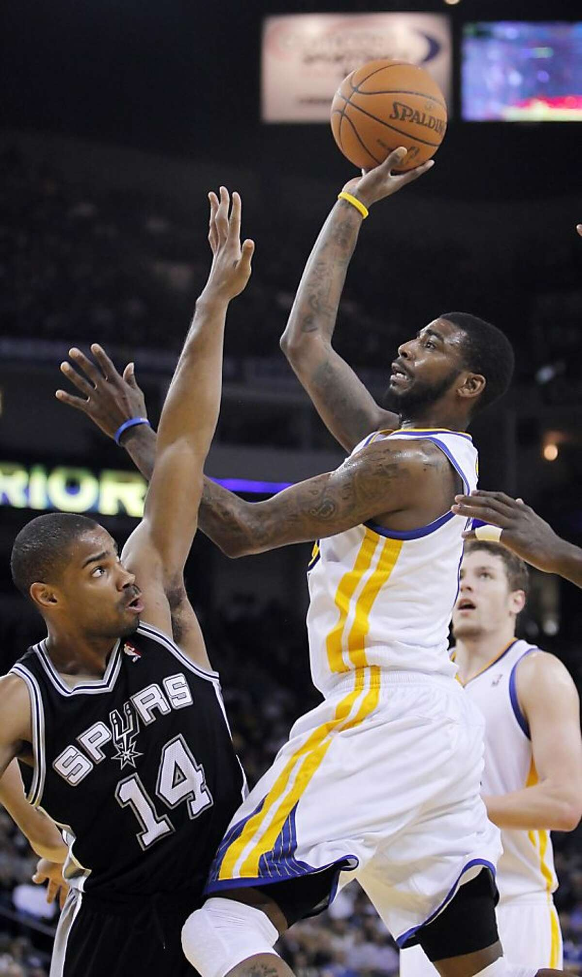 The Warriors' Dorell Wright puts up a shot in the fourth quarter over San Antonio's Gary Neal at Oracle Arena in Oakland on Monday.