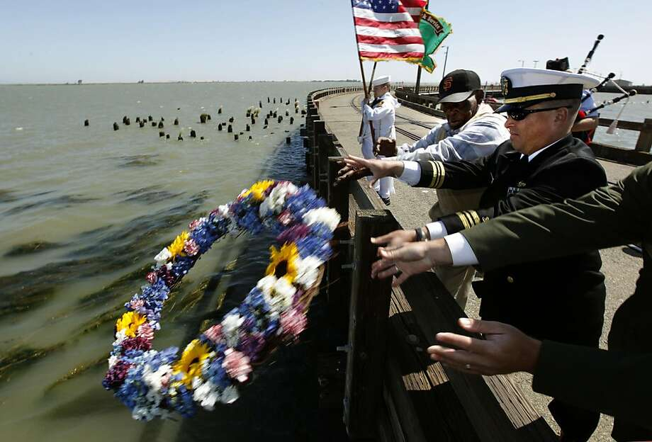 91-year-old survivor, T.J. Hart, (left), of Pittsburg, joins Carlos Gonzales , Lt. Commander of the 834th Transportation Battalion, as they place a wreath into the waters at the site of the explosion. The 320 men who lost their lives in the July 17, 1944 munitions explosion, are remembered during a memorial ceremony at the Military Ocean Terminal Concord , in Concord, Ca. on Saturday July 23, 2011. Photo: Michael Macor, The Chronicle