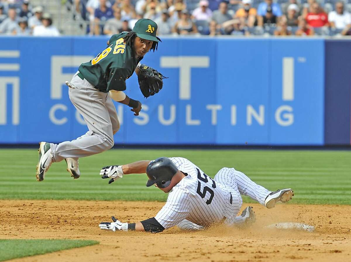 Oakland Athletics shortstop Jemile Weeks jumps out of the way of a sliding Russell Martin of the New York Yankees on a ninth-inning double play at Yankee Stadium in New York on Saturday, July 23, 2011. The A's held off the Yankees, 4-3. (David Pokress/Newsday/MCT)