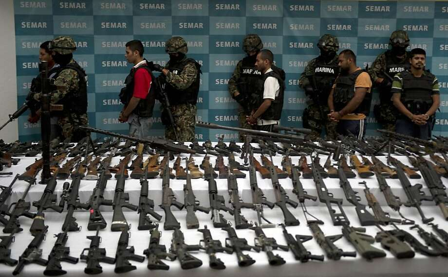 Mexican marines escort five alleged drug traffickers of the Zetas drug cartel in front of hand grenades, firearms, cocaine and military uniforms seized to alleged members of the Zetas drug traffickers cartel. Photo: Yuri Cortez, AFP/Getty Images