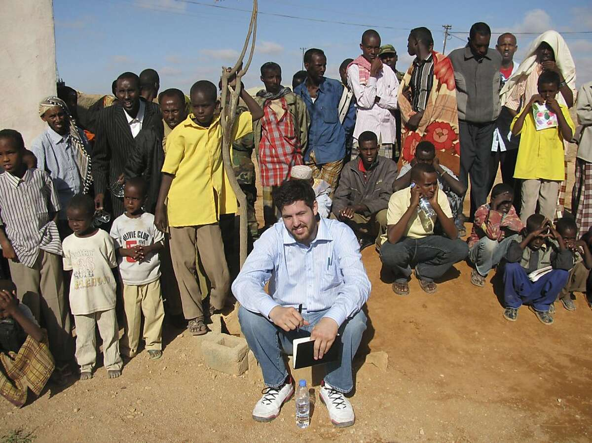 A June 1, 2009, photo of Canadian author Jay Bahadur posing with Somali villagers in Dhanane, the semiautonomous region of Puntland, Somalia, while researching a book about piracy.