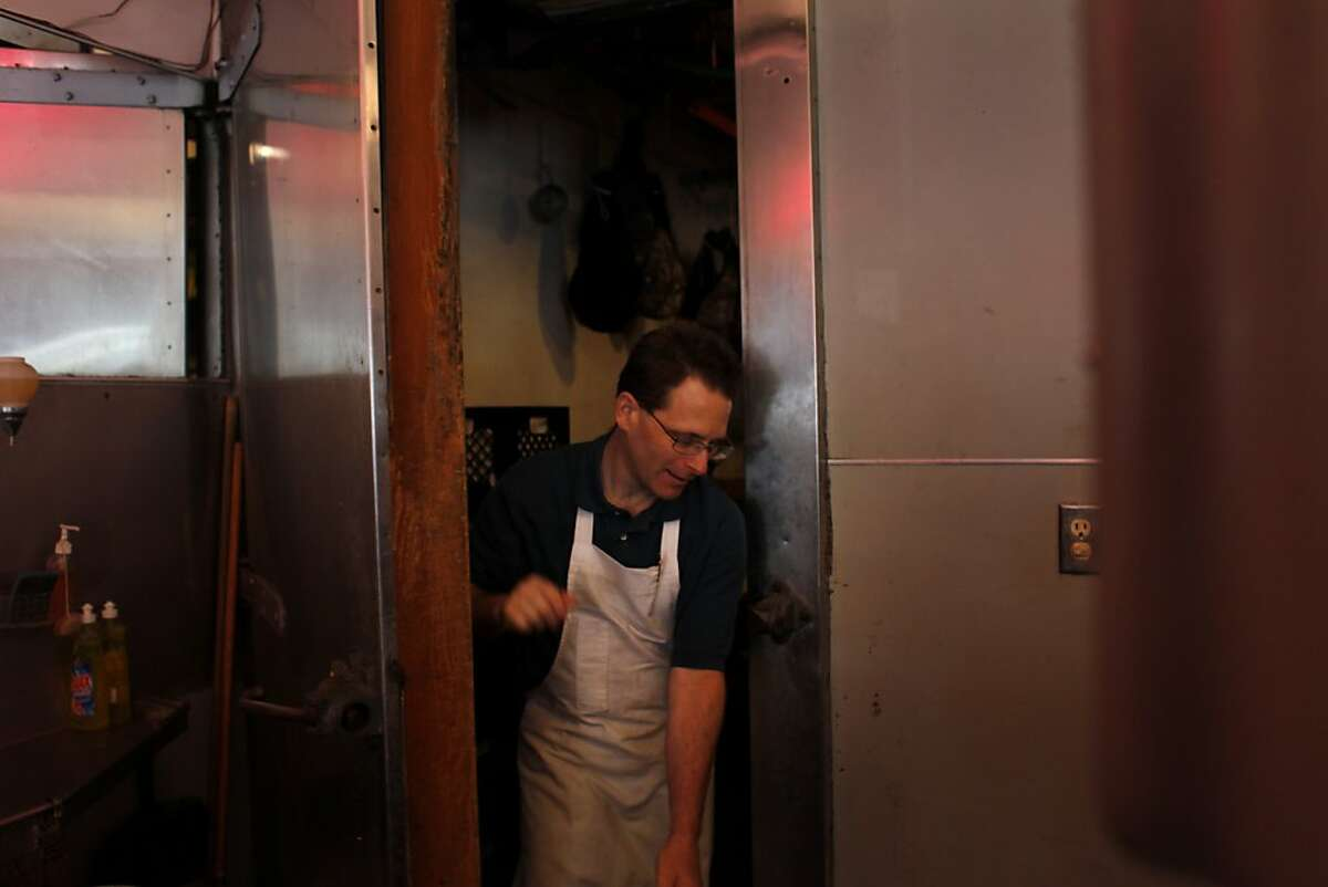 Mike Spinali, 44, who first started working at the Little City Market as a summer job at the age of 15, walks out of the meat locker inside the store.