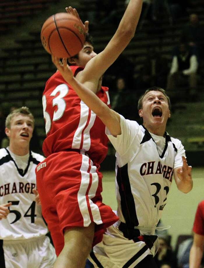 Churchill's Ben Mammel (32) attempts a layup against Judson's David Wacker (33) in boys basketball at Littleton Gym on Tuesday, Dec. 6, 2011. Mammel scored three big baskets in the fourth quarter to help the Chargers defeat the Rockets, 52-44. Photo: KIN MAN HUI, ~ / SAN ANTONIO EXPRESS-NEWS