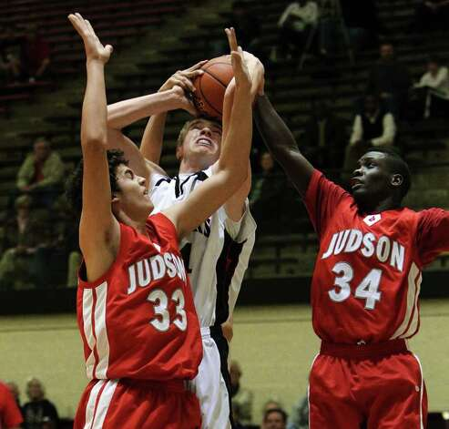 Churchill's Connor Lammert (center) gets tangled in a rebound with Judson's David Wacker (33) and Sheawn Bedford (34) in boys basketball at Littleton Gym on Tuesday, Dec. 6, 2011. The Chargers defeated the Rockets, 52-44. Photo: KIN MAN HUI, ~ / SAN ANTONIO EXPRESS-NEWS