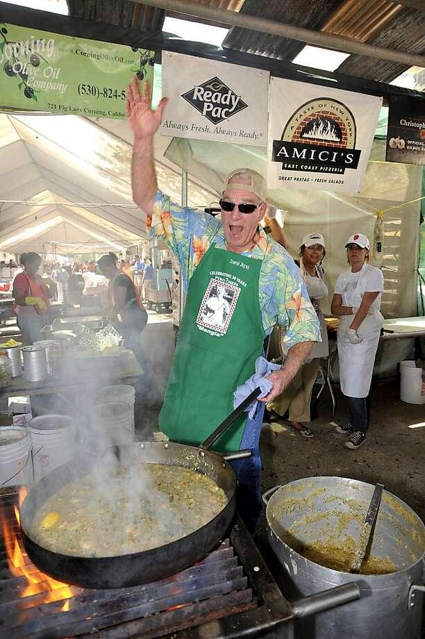 A Garlic Festival pyro chef displays a skillet of scampi on Gourmet Alley. Photo: Bill Strange, Gilroy Garlic Festival