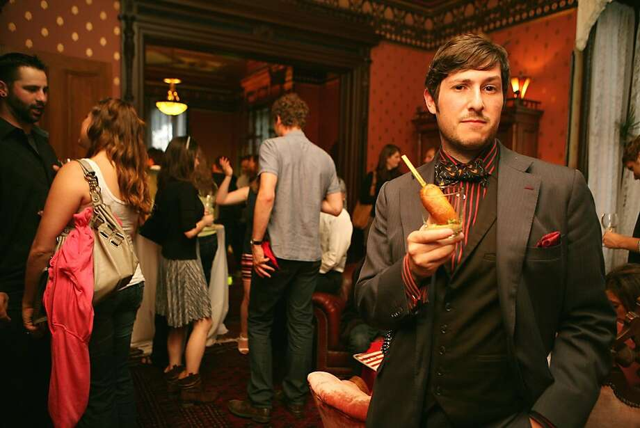 Noble Rot host curator Jonathan Cristaldi enjoys a snail corn dog at the Stag Dining Group Anti-Bastille Day Celebration July 14, 2011, in San Francisco. Photo: Sarah Adler, The Chronicle