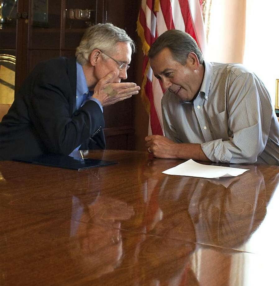 Senate Majority Leader Harry Reid, D-Nev., whispers to House Speaker John Boehner, R-Ohio, during a photo opportunity in the House Speaker's office before a meeting on the debt limit increase on Capitol Hill in Washington on Saturday, July 23, 2011. Photo: Harry Hamburg, AP