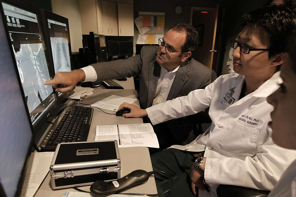 The Chief of Neurosugery, Dr. Geoff Manley, (left) meets with chief resident MIchael Oh and Dr. Emily Anton as they go over the patients information from the night before at San Francisco General Hospital, in San Francisco, on Friday June 29, 2011. Dr. Manley is currently taken care of San Francisco Giants fan, Bryan Stow, who was badly beaten on opening night of the baseball season in Los Angeles and remains in a coma 3 1/2 months later.