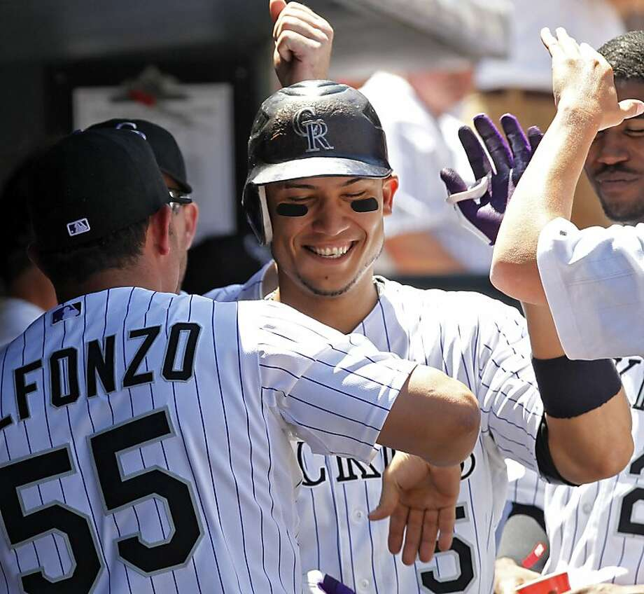 Colorado Rockies Carlos Gonzalez, center, is congratulated in the dugout  after his solo home run against the Atlanta Braves in the first inning of a baseball game at Coors Field in Denver on Thursday, July 21, 2011. Photo: Ed Andrieski, AP