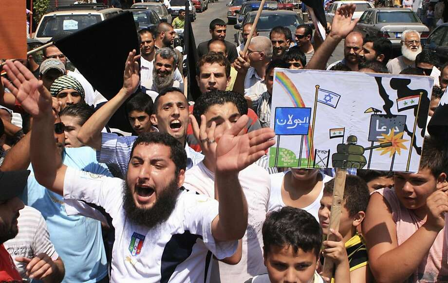 """Lebanese protesters shout slogans as they march during a rally in solidarity with Syrian anti-government protesters in the northern city of Tripoli, Lebanon, Friday, July 22, 2011. The drawing depicts an armored vehicle firing towards Daraa while the calmreigns in the Israeli-controlled Golan Heights, left."""" Photo: Str, AP"""