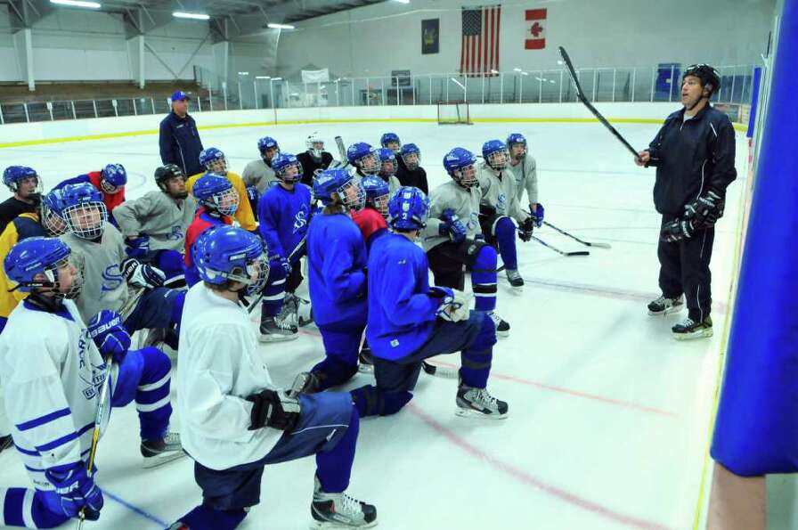 Saratoga Springs High School hockey team assistant coach Tim Grande, right, talks to the team during