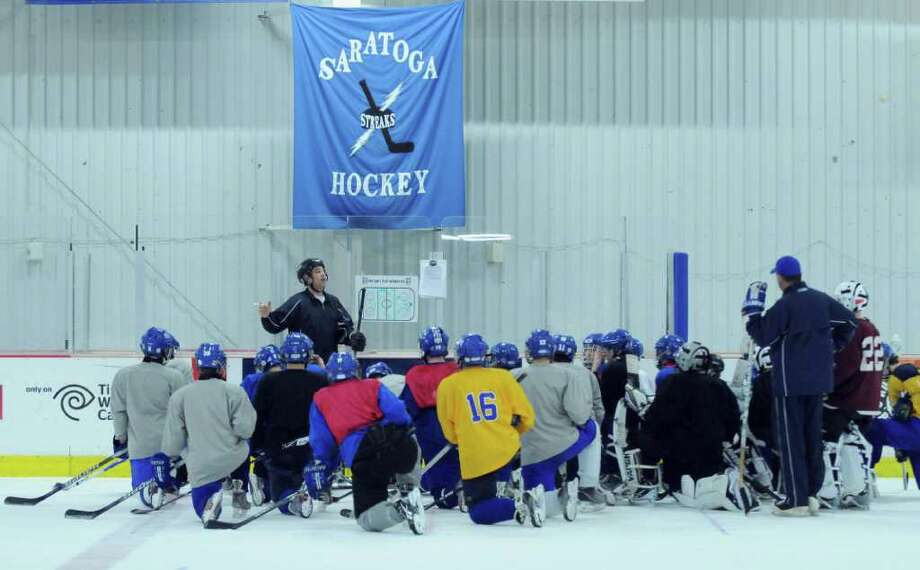 Saratoga Springs High School hockey team assistant coach Tim Grande, left, talks to the team during practice on Tuesday Dec. 6, 2011 in Saratoga Springs, NY.  (Philip Kamrass / Times Union ) Photo: Philip Kamrass / 00015660A