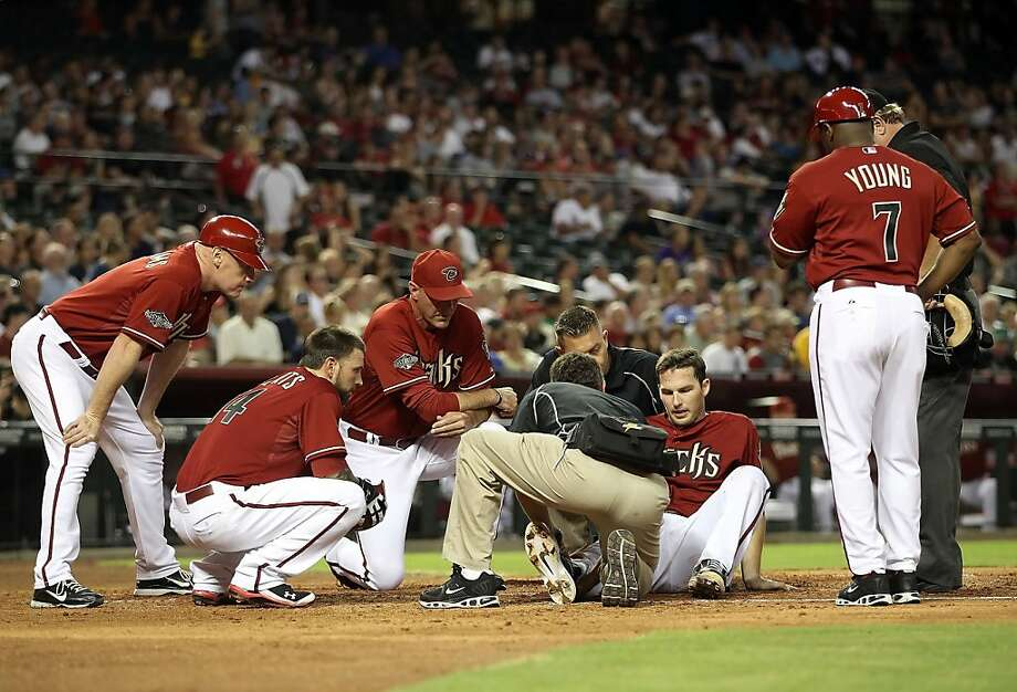 PHOENIX, AZ - JULY 20:  Stephen Drew #6 of the Arizona Diamondbacks is looked at by trainers, manger Kirk Gibson, Ryan Roberts #14 and coaches after he was injured attempting to score against the Milwaukee Brewers during the fifth inning of the Major League Baseball game at Chase Field on July 20, 2011 in Phoenix, Arizona. Drew was injured on the play and taken out of the game. Photo: Christian Petersen, Getty Images