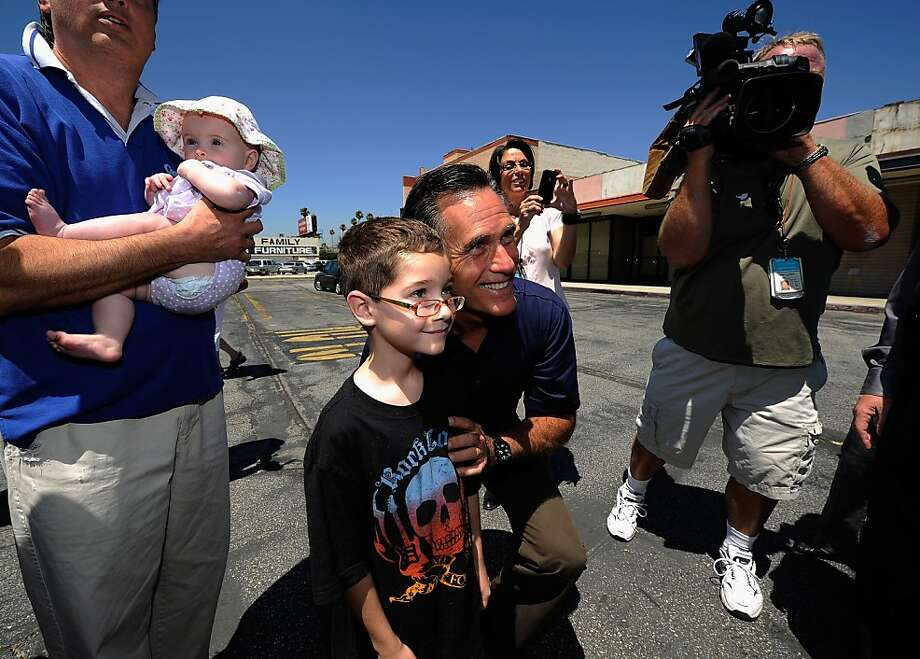Republican presidential candidate and former Massachusetts Gov. Mitt Romney poses with Garrett White, 8 in front of vacant stores of the Valley Plaza shopping center during a campaignstop on July 20, 2011 in Los Angeles, California.  Romney criticized President Barack Obama's handling of the economy during the brief campaign event. Photo: Kevork Djansezian, Getty Images
