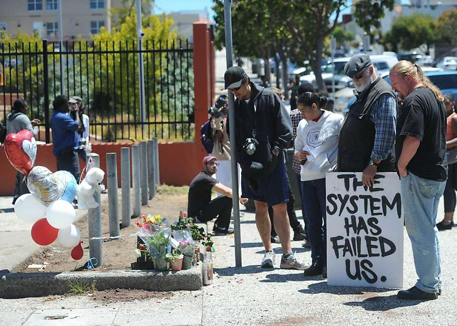 People including Lori Davis (2nd from left ) and Doug Norberg (next to Lori) look at a memorial set up for Kenneth Harding at the corner of Oakdale and 3rd Street in San Francisco on July 18, 2011. A rally was held in demonstration against the police involved fatal shooting. Photo: Susana Bates, Special To The Chronicle