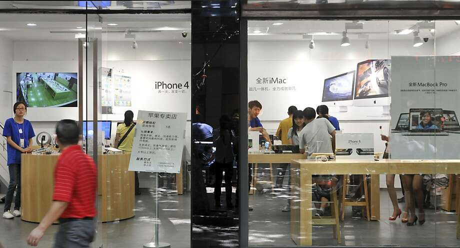 A man walks past windows of a shop masquerading as a bona fide Apple store in downtown Kunming, in southwest China's Yunnan province, Thursday, July 21, 2011. China, long known for producing counterfeit consumer gadgets, software and brand name clothing, has reached a new piracy milestone - fake Apple stores. (AP Photo)  CHINA OUT Photo: AP
