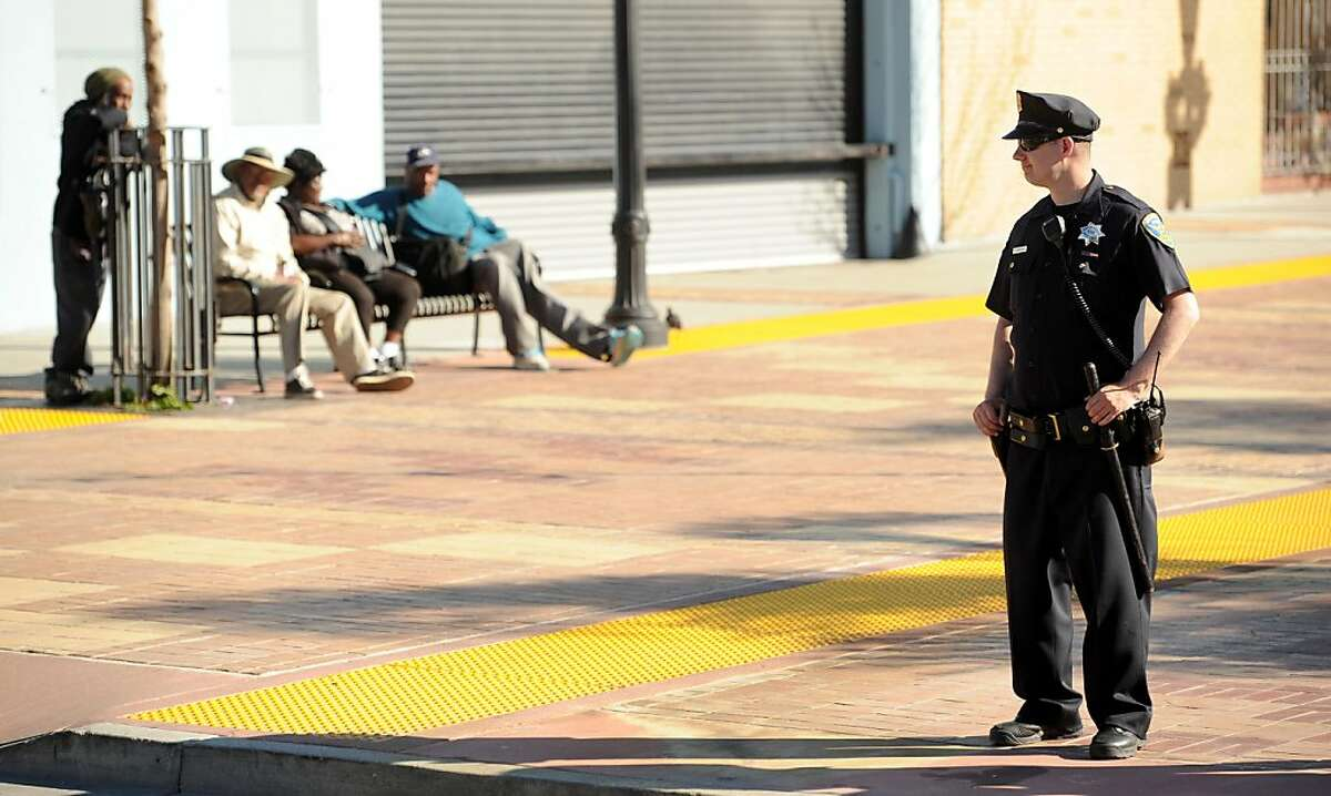 San Francisco police Officer Bartley keeps watch outside a Bayview community meeting on Wednesday, July 20, 2011, in San Francisco. About 300 people, many upset about the police shooting of Kenneth Wade Harding, gathered for the meeting which ended early following outbursts from some attendees.