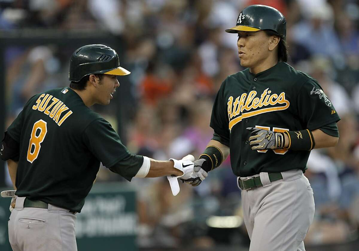 Oakland Athletics designated hitter Hideki Matsui, of Japan, right, is congratulated by Kurt Suzuki (8) after hitting a solo home run during the sixth inning of a baseball game against the Detroit Tigers, Wednesday, July 20, 2011, in Detroit.