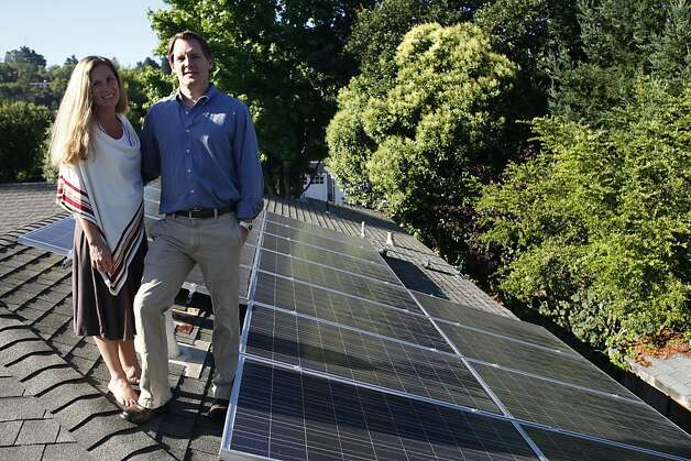 Ted Lieser and Suzanna Dibianca stand on their roof in Mill Valley, Calif. where they use leased solar panels on July 20, 2011. With a solar lease, a company such as San Francisco's SunRun will install, own and maintain solar panels on your home, while you pay for the electricity the panels produce. You get the power without having to pay for the panels. Solar leases for homeowners didn't exist five years ago, but they've quickly become common. Photo: Maddie McGarvey, The Chronicle