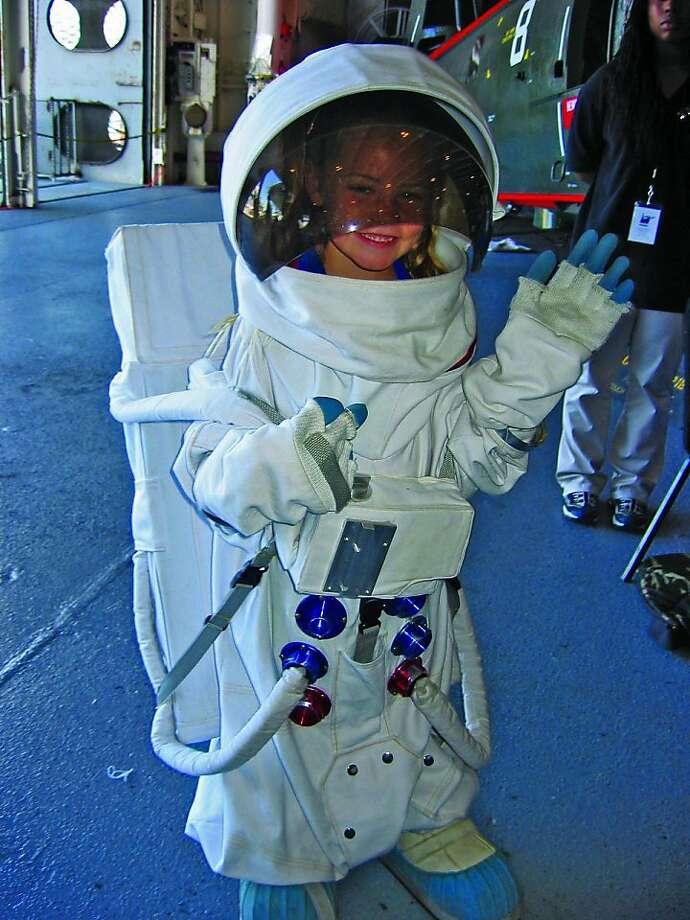 A little girl explores a spacesuit at the USS Hornet. Photo: USS Hornet