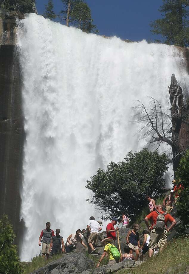 Hikers approach Vernal Fall, background, in Yosemite National Park in California on Wednesday, July 20, 2011, a day after three visitors reportedly died after getting swept over the waterfall. (Eric Paul Zamora/Fresno Bee/MCT) Photo: Eric Paul Zamora, MCT