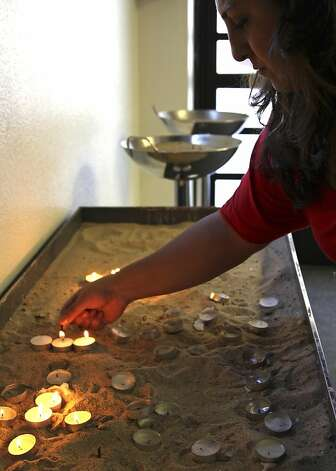 Diana David lights candles during a vigil held for 3 missing hikers at the Holy Apostolic Catholic Assyrian Church of the East, Wednesday, July 20, 2011, in Ceres, Calif. Three people are presumed dead after being swept over a raging waterfall in YosemiteNational Park on Tuesday. The three were believed to be in Yosemite as part of a modesto based youth church outing. Photo: Ben Margot, AP