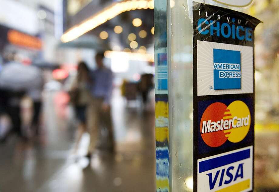 Signs for American Express, Master Card and Visa credit cards are shown on a New York store's door on in this July 23, 2007 file photo. Americans are falling behind on their credit card payments at an alarming rate, sending delinquencies and defaults surging by double-digit percentages in the last year and prompting warnings of worse to come. Photo: Mark Lennihan, AP