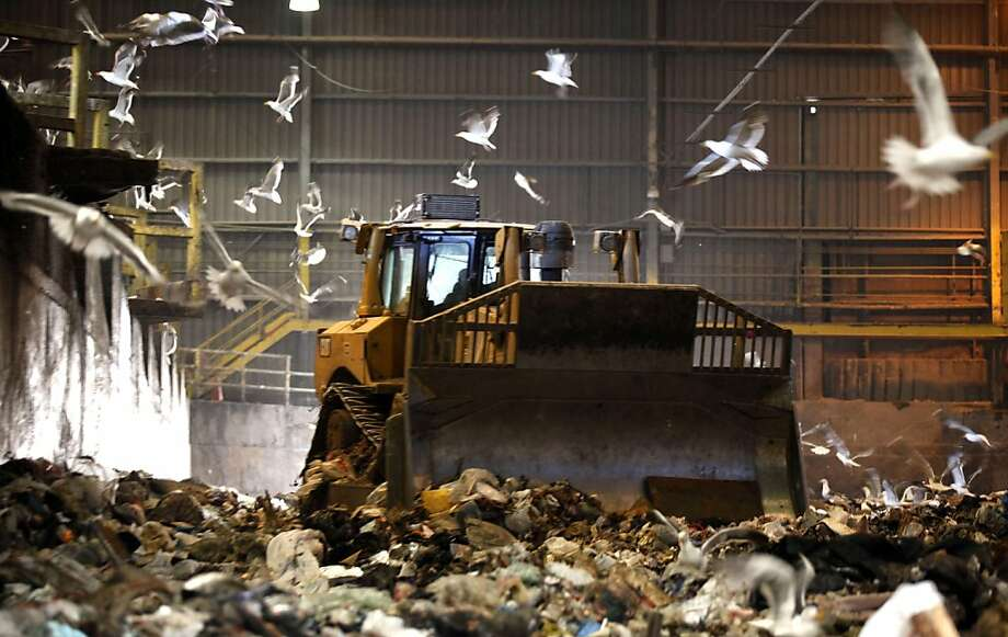 Bulldozers crush garbage before itês loaded onto large trucks that take the material to landfills. Recology's transfer station is one of the busiest places for the company.  San Francisco is preparing to award a new landfill contract to Recology, the garbage company that picks of the city's rubbish, recyclables and compostable Wednesday July 20, 2011. Photo: Lance Iversen, The Chronicle
