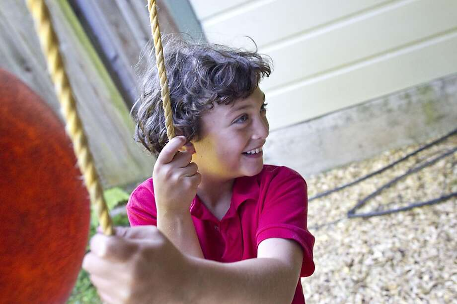 Jonah Fox, a 10-year-old who has autism, works on learning to swing with his therapist during a behavioral therapy session at his home in San Francisco, Calif., on Tuesday, July 19, 2011. Photo: Laura Morton, Special To The Chronicle