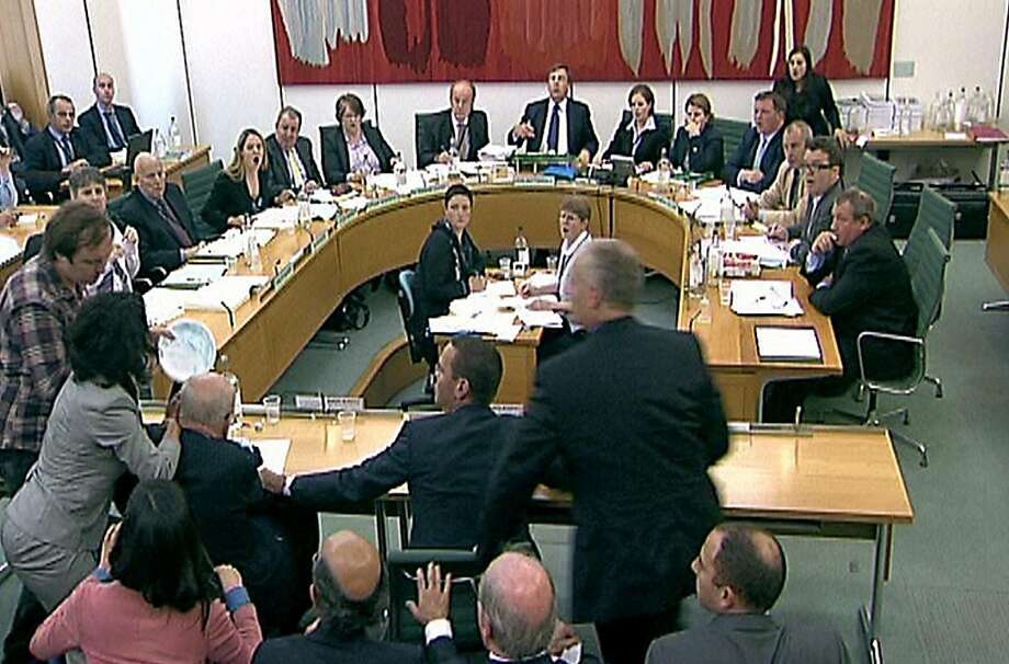 Committee members react after a protestor (left checked shirt), named on Twitter as Jonnie Marbles, tries to throw a paper plate covered in shaving foam over Rupert Murdoch as he gave evidence to the Culture, Media and Sport Select Committee in the House of Commons in central London on the News of the World phone-hacking scandal in London, Great Britain, on July 19, 2011. (PA Photos/Abaca Press/MCT) Photo: PA Photos, MCT