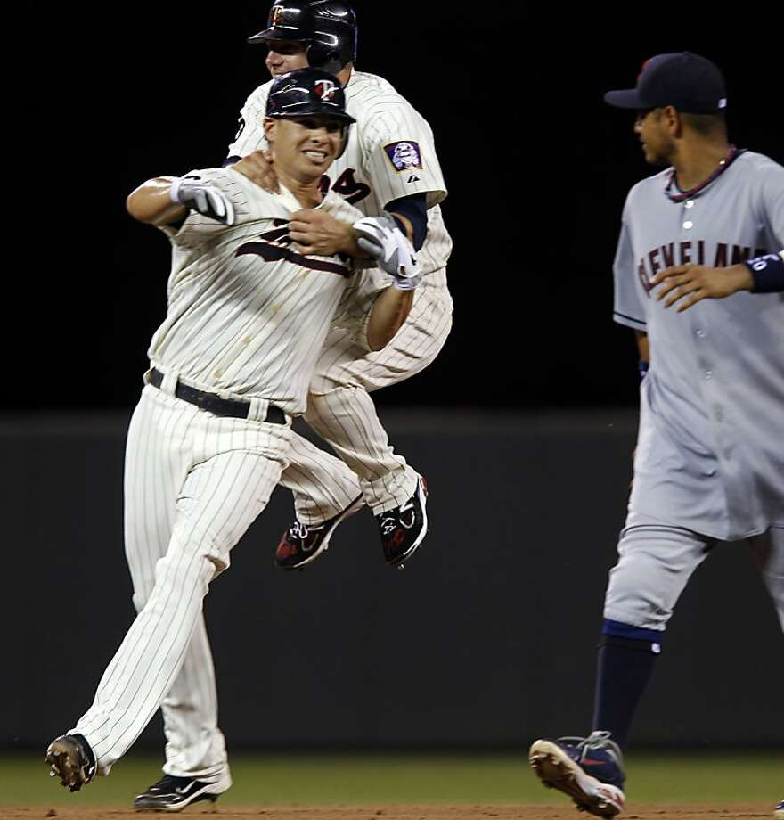 Minnesota Twins' Danny Valencia, left, is congratulated by teammate Luke Hughes, after hitting a two-run single to beat the Cleveland Indians 2-1 in a baseball game Tuesday, July 19, 2011, in Minneapolis.  At right is Indians' Orlando Cabrera. Photo: Genevieve Ross, AP