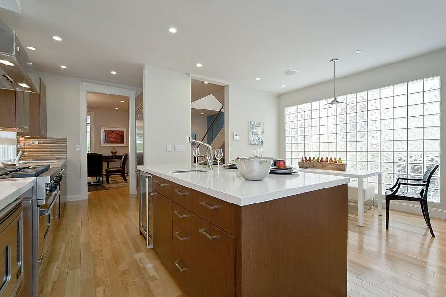 The kitchen, which includes a center island with a sink, opens to an eating area. Photo: OpenHomesPhotography.com