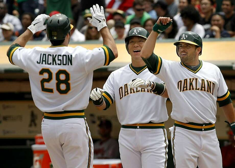 Conor Jackson is welcomed home by Hideki Matsui and David DeJesus (right) after Jackson's first inning grand slam against the Los Angeles Angels at the Oakland Coliseum on Sunday. Photo: Brant Ward, The Chronicle