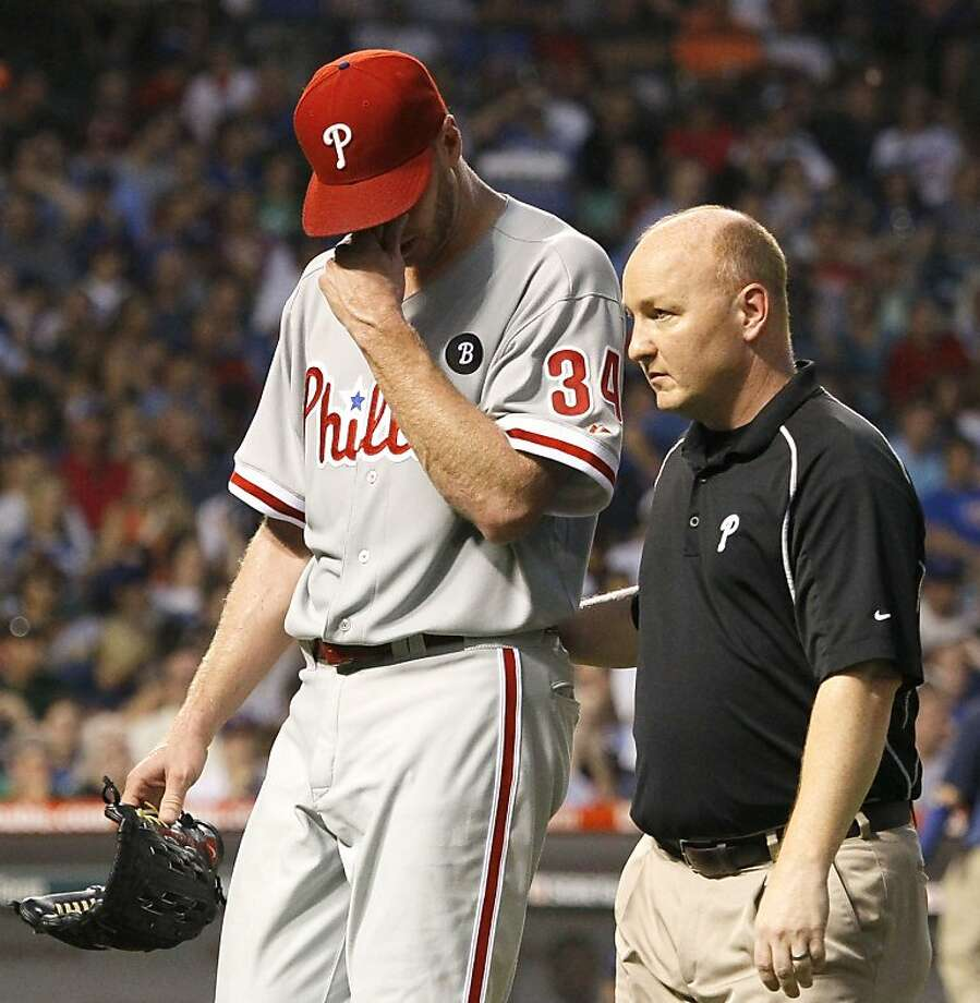 Philadelphia Phillies' Roy Halladay, left, leaves the game with trainer Scott Sheridan during the fifth inning of a baseball game against the Chicago Cubs Monday, July 18, 2011 in Chicago. Photo: Charles Rex Arbogast, AP