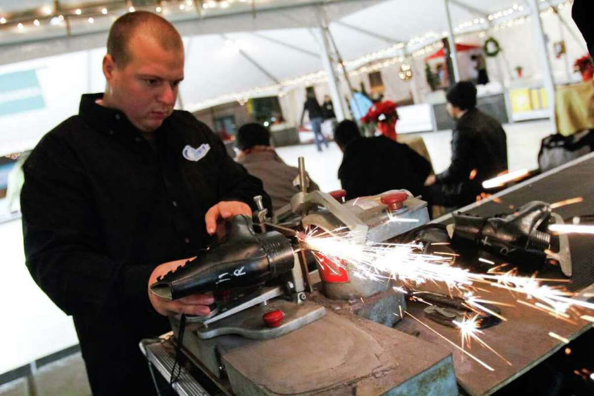 David Tibbetts sharpens rental skates before they are used at the Capitol Hill Ice Rink located at Cal Anderson Park in Seattle on Dec. 6, 2011. The ice rink does not actually contain any ice -- it utilizes polyurethane and a liquid to simulate the feel of ice skating.